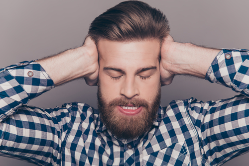 bearded man with closed eyes covering ears with hands.