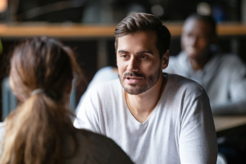 Young serious man having conversation with woman girlfriend sit at cafe table