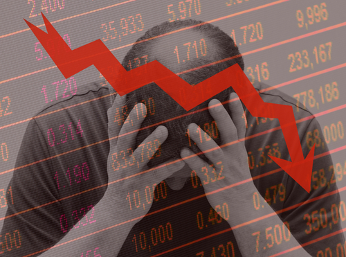 middle aged man holding his head in his hands while the markets plunge on a descending stock curve background.