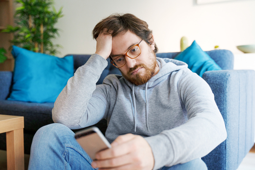 Single lonesome guy checking cell on the couch