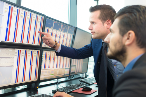 Stock traders looking at graphs, indexes and numbers on multiple computer screens.